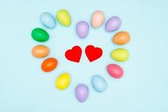Les oeufs de pâques colorés autour du coeur forment, des valentines Images stock