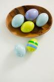 Les oeufs de pâques colorés dans la cuvette avec deux ont peint des oeufs de pâques Photographie stock libre de droits