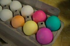 Les oeufs de pâques colorés dans le carton d'oeufs pour l'oeuf de pâques chassent Photo stock