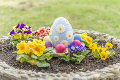 Les oeufs de pâques colorés dans un pot de fleur avec la violette à cornes fleurit Image stock