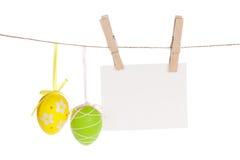 Les oeufs de pâques colorés et la photo vide encadrent accrocher sur la corde Photos libres de droits