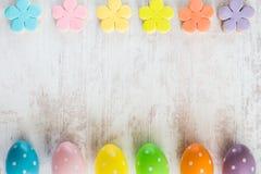 Les oeufs de pâques colorés et le fondant fait maison ont couvert des biscuits de fleur sur un fond en bois blanc Image libre de droits