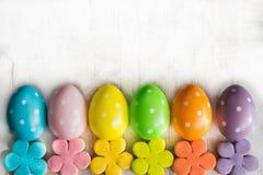Les oeufs de pâques colorés et le fondant fait maison ont couvert des biscuits de fleur sur un fond en bois blanc Images libres de droits