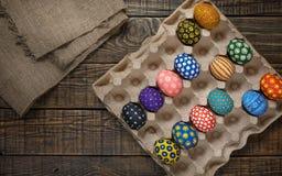 Les oeufs de pâques colorés sur le fond en bois textotent à une toile à sac Photos stock