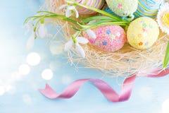 Les oeufs de pâques dans le nid avec le ressort fleurit Photographie stock libre de droits