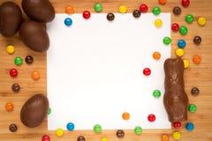 Les oeufs de pâques de chocolat, la dragée de sucrerie, lapin de Pâques sur une lumière courtisent Images stock