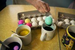 Les oeufs de pâques de coloration avec le colorant est une tradition de vacances d'amusement images stock