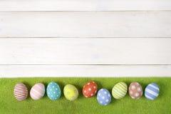 Les oeufs de pâques faits main colorés se trouvent sur une pelouse verte sur un fond en bois blanc style plat de configuration Photo libre de droits