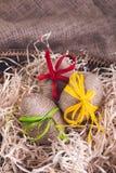 Les oeufs de pâques ont enveloppé la ficelle de laine dans le panier brun sur le fond en bois rustique avec la toile à sac heureu Photos stock