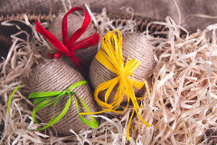 Les oeufs de pâques ont enveloppé la ficelle de laine dans le panier brun sur le fond en bois rustique avec la toile à sac heureu Image libre de droits