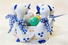 Les oeufs de pâques peints à la main dans le blanc avec le vase bleu avec des canards figure Photographie stock