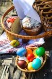 Les oeufs et les gâteaux de pâques sont dans le panier sur une table en bois Photographie stock libre de droits