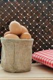 Les oeufs frais de poulet dans le sac sur la table et le bambou en bois tissent le backg Photographie stock