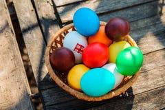Les oeufs multicolores se situent dans un panier sur une table en bois dehors Photographie stock libre de droits