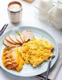 Les oeufs ont brouillé, omelette avec le poivron doux grillé de cloche et poulet smocked chaud, jambon dans un plat sur un fond b Photographie stock