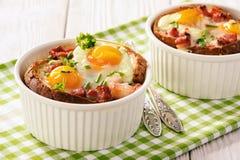 Les oeufs ont fait cuire au four avec le lard, les tomates, l'ail et le pain Images libres de droits