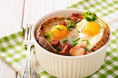 Les oeufs ont fait cuire au four avec le lard, les tomates, l'ail et le pain Photographie stock libre de droits