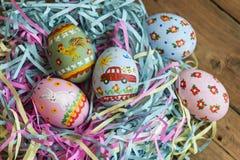 Les oeufs peints se situent dans un panier, fond en bois, Pâques photo libre de droits