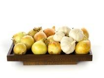Les oignons et l'ail ont présenté sur un panneau en bois Image stock