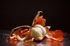 Les oignons ont épluché avec la cosse sur un fond foncé photographie stock libre de droits