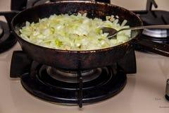 Les oignons ont fait frire dans une casserole images libres de droits