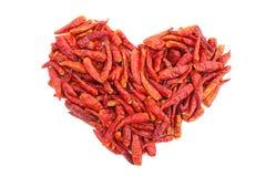 Les oiseaux rouges épicés observent des poivrons de piments dans une forme de coeur Photographie stock
