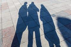 Les ombres de trois personnes sur des tuiles d'un trottoir Images libres de droits