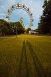 Les ombres des deux personnes sur l'herbe contre les ferris roulent dedans le parc à Vienne, Autriche Images libres de droits