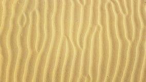 Les ondulations de sable donnent au modèle une consistance rugueuse formé avec le vent violent sur la plage arénacée d'été image stock