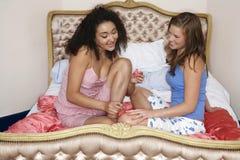 Les ongles de l'ami de peinture d'adolescente sur le lit Photo stock
