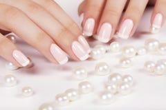 Les ongles de la belle femme avec la manucure française Photographie stock libre de droits