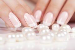 Les ongles de la belle femme avec la manucure française Photos stock