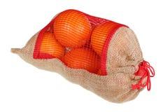 Les oranges de Noël dans un sac fait maison de toile rustique ont isolé image stock