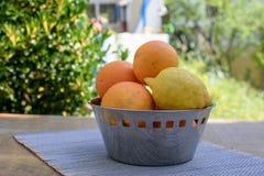 Les oranges et les citrons se situent dans une tasse sur la table Photos libres de droits