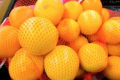 Les oranges ont empaqueté dans les sacs nets à une épicerie images libres de droits