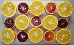 Les oranges sanguines rouges rouges et les oranges navel ont coupé dans la moitié Image stock