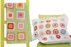 Les oreillers faits main sur la chaise et la couverture ont drapé au-dessus d'un decorat Photographie stock libre de droits