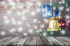 Les ornements de boîte-cadeau de Noël accrochent sur l'arbre de Noël avec du bois de perspective Image libre de droits