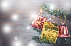 Les ornements de boîte-cadeau de Noël accrochent sur l'arbre de Noël ont le fond en bois de l'espace Photo stock