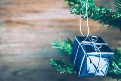 Les ornements de boîte-cadeau de Noël accrochent sur l'arbre de Noël ont le fond en bois de l'espace Photos libres de droits