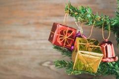 Les ornements de boîte-cadeau de Noël accrochent sur l'arbre de Noël ont le fond en bois de l'espace Image stock
