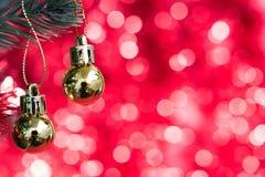 Les ornements de Noël décorent sur l'arbre de sapin avec le bokeh d'or Photos libres de droits