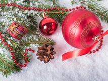 Les ornements et le sapin d'arbre de Noël s'embranchent sur la neige image libre de droits