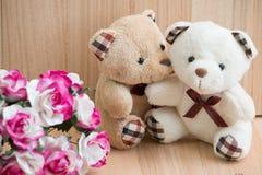 Les ours d'étreinte dans l'amour se reposent près du bouquet se sont levés Photographie stock libre de droits