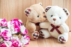 Les ours d'étreinte dans l'amour se reposent près du bouquet se sont levés Photographie stock