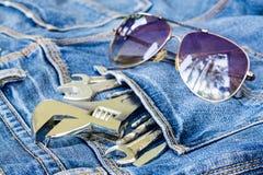 Les outils dans des jeans empochent avec le concept de fond de lunettes de soleil Photos libres de droits