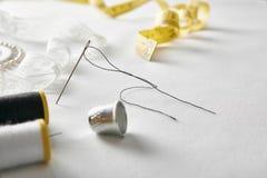 Les outils de couture avec la dentelle sur le fond blanc de tissu ont élevé la vue Images stock