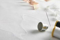 Les outils de couture avec la dentelle sur le tissu blanc ont élevé la vue diagonale Photo libre de droits
