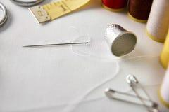 Les outils de couture sur le fond blanc de tissu ont élevé la vue Photographie stock libre de droits
