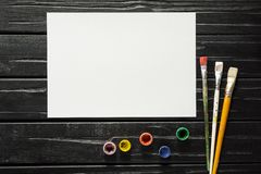 Les outils de l'artiste, des brosses, des peintures et de la toile ne sont pas fond en bois foncé images stock